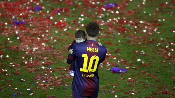 Barcelona's Lionel Messi carries his son Thiago during the Spanish league first division trophy celebrations at Camp Nou stadium in Barcelona